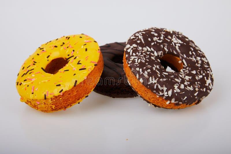 Asortowani donuts z czekoladą oszroniejącą, kolor żółty glazurowali donuts i kropią obrazy royalty free
