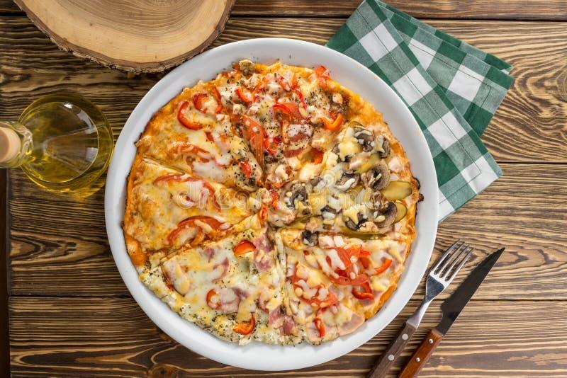 Asortowani pizza kawałki z baleronem, pieczarka, pomidorowy odgórny widok na drewnianym stole zdjęcia stock