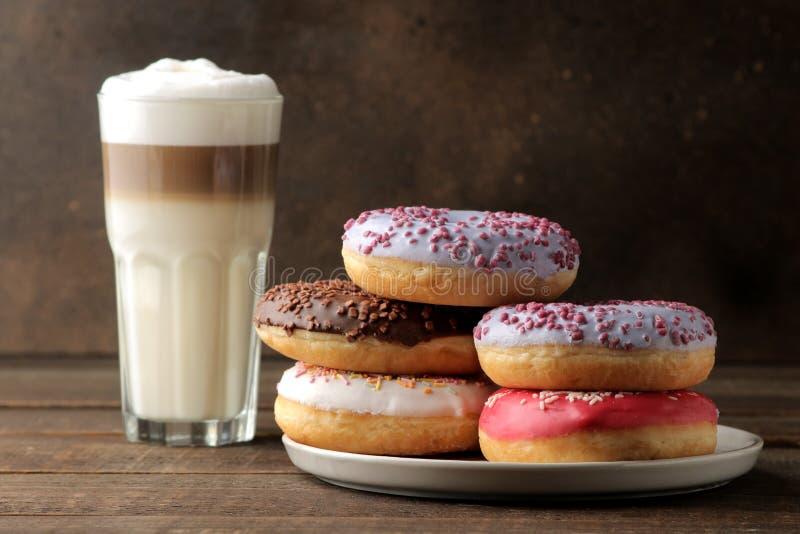 Asortowani słodcy donuts z, kawowy latte na brązu drewnianym stole, i obraz stock