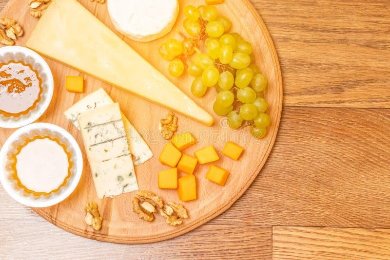 Asortowani sery na round drewnianej deski talerzu zdjęcie stock