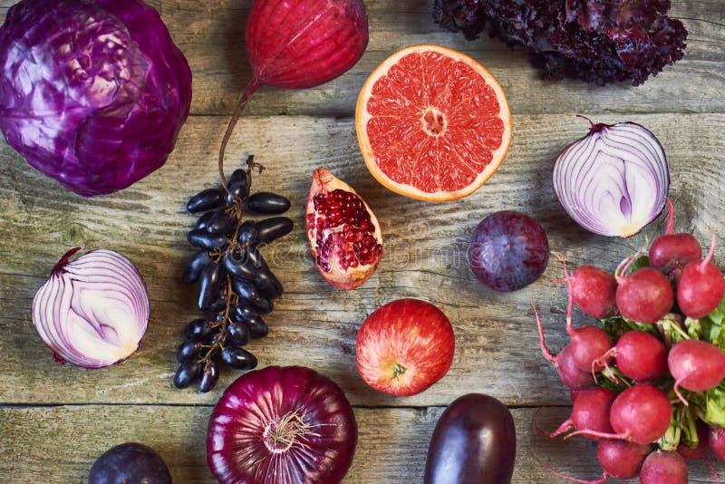 Asortowani typy purpurowi owoc i warzywo na drewnianym backgro obrazy stock