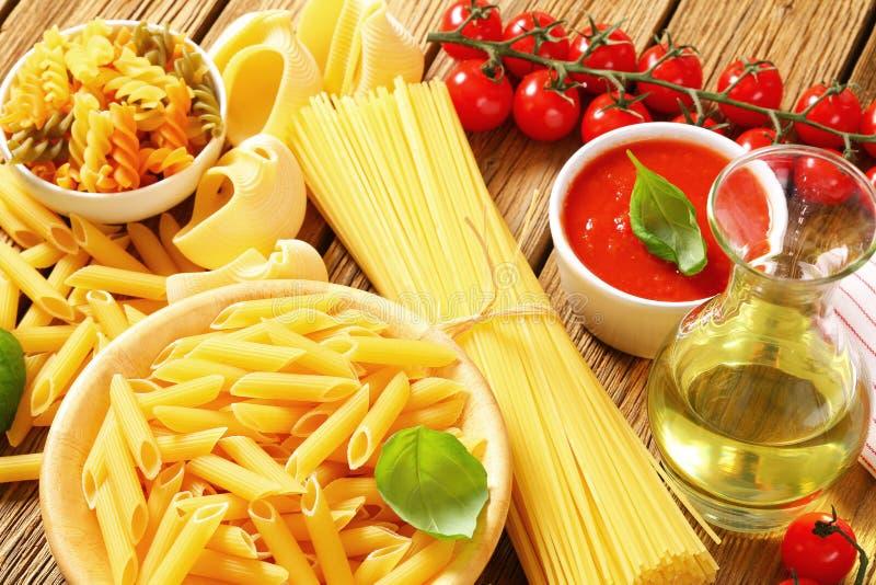 Asortowany makaron, pomidorowy passata i oliwa z oliwek, obrazy stock