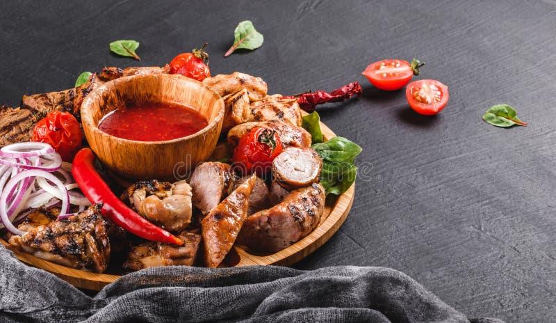 Asortowany wy?mienicie piec na grillu mi?so i kie?basy z pomidorami i bbq kumberlandem na tn?cej desce nad czerni? drylujemy t?o  zdjęcie stock