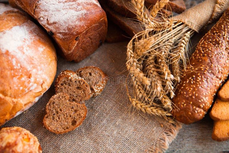 Asortyment świeży piec chleb na drewnianym stołowym tle obrazy royalty free