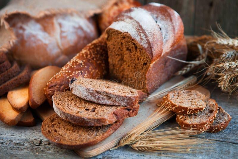 Asortyment świeży piec chleb na drewnianym stołowym tle zdjęcie stock