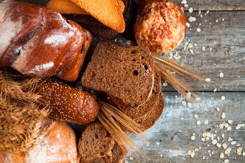 Asortyment świeży piec chleb na drewnianym stołowym tle zdjęcia royalty free