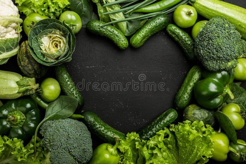 Asortyment świezi zieleni warzywa w kierowym kształcie na ciemnym tle zdjęcie stock