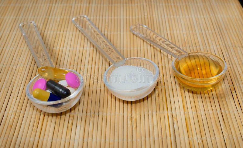 Asortyment farmaceutyczni przygotowania na łyżkach, pastylkach, kapsułach, syropie i proszku, Na bambusowej macie fotografia stock