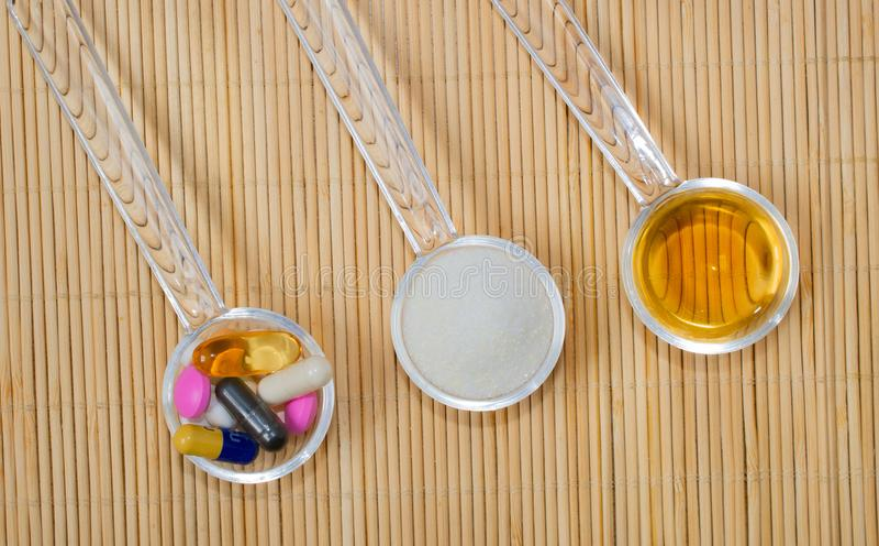 Asortyment farmaceutyczni przygotowania na łyżkach, pastylkach, kapsułach, syropie i proszku, Na bambusowej macie zdjęcie royalty free