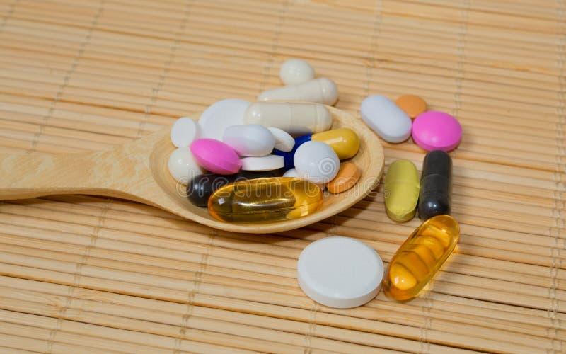 Asortyment farmaceutyczni przygotowania na drewnianych łyżkach, pastylki, kapsuły Na bambusowej macie obraz stock