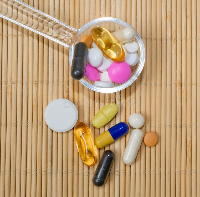 Asortyment farmaceutyczni przygotowania, pastylki i kapsuły na łyżce na bambus macie, obraz royalty free