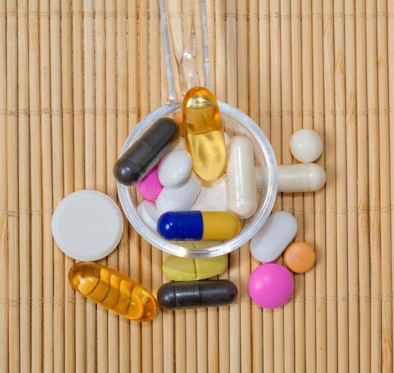 Asortyment farmaceutyczni przygotowania, pastylki i kapsuły na łyżce na bambus macie, fotografia royalty free