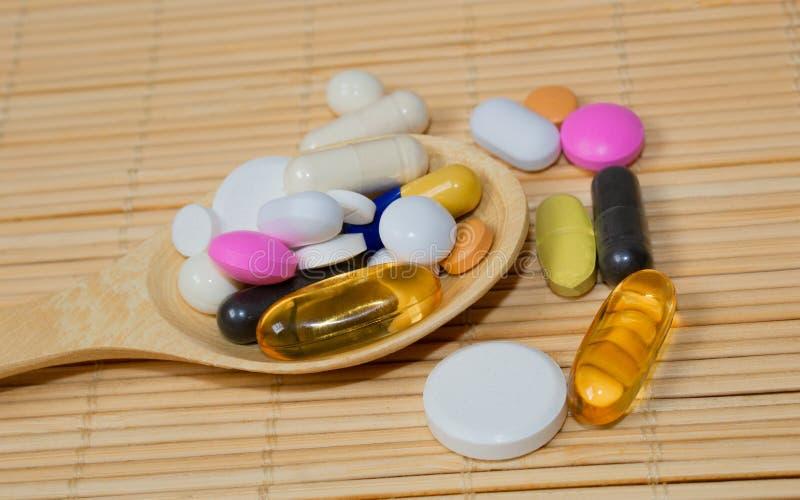 Asortyment farmaceutyczni przygotowania, pastylki i kapsuły na łyżce na bambus macie, zdjęcie royalty free