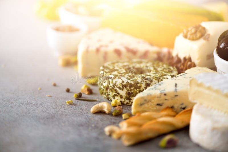 Asortyment mocno, miękka część i miękcy sery z oliwkami, grissini chlebowi kije, kapary, winogrono, na popielatym betonie fotografia stock