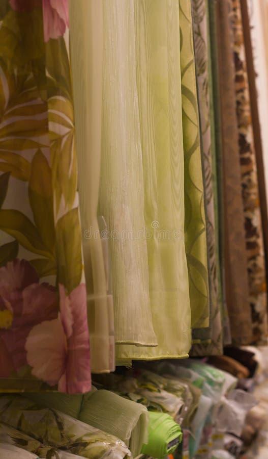 Asortyment piękne zasłony obwieszenia próbki w sklepowej tkaniny pionowym zakończeniu up obrazy royalty free