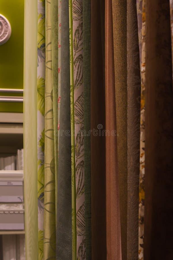 Asortyment piękne zasłony obwieszenia próbki w sklepowym pionowym zakończeniu up zdjęcia stock