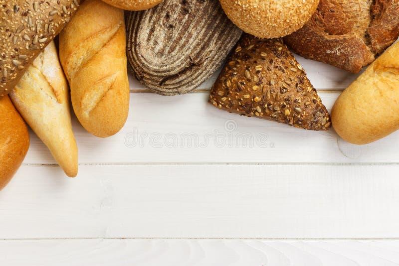 Asortyment piec chleb na białym drewnianym stołowym tle Odgórny widok z kopii przestrzenią obrazy royalty free