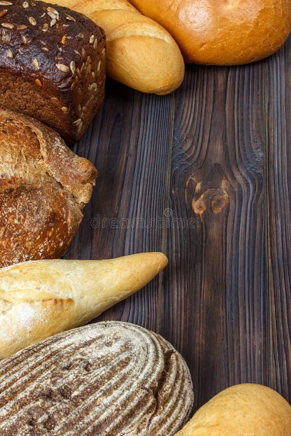 Asortyment piec chleb na ciemnym drewnianym tle Piekarni i sklepu spożywczego sklepu spożywczego pojęcie Mieszkanie kłaść z przes fotografia royalty free