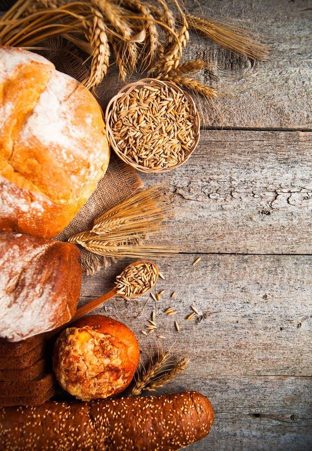 Asortyment piec chleb na starym drewnianym stołowym tle fotografia stock