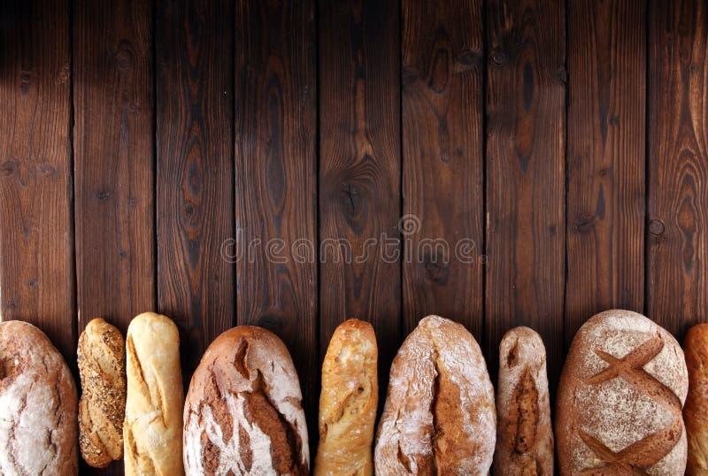 Asortyment piec chlebowe i chlebowe rolki na drewnianym stołowym tle obraz stock
