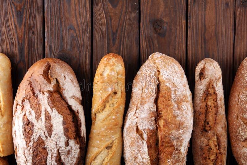 Asortyment piec chlebowe i chlebowe rolki na drewnianym stołowym tle fotografia stock