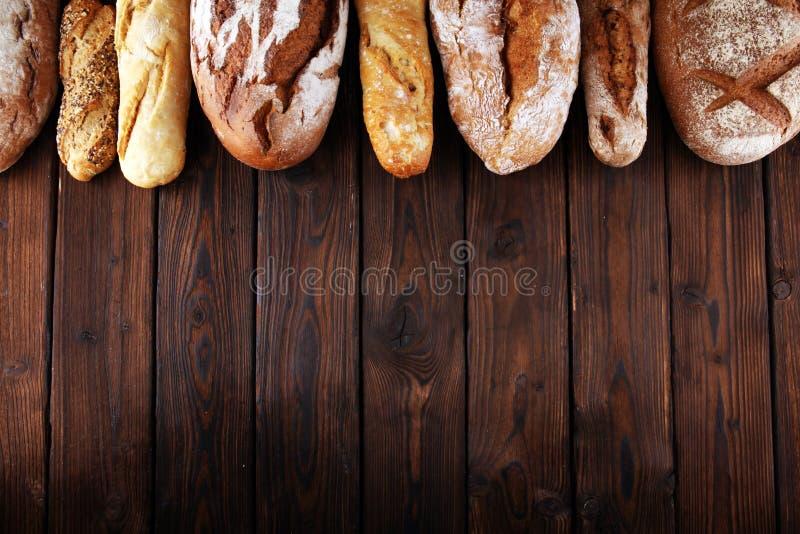 Asortyment piec chlebowe i chlebowe rolki na drewnianym stołowym tle zdjęcia royalty free