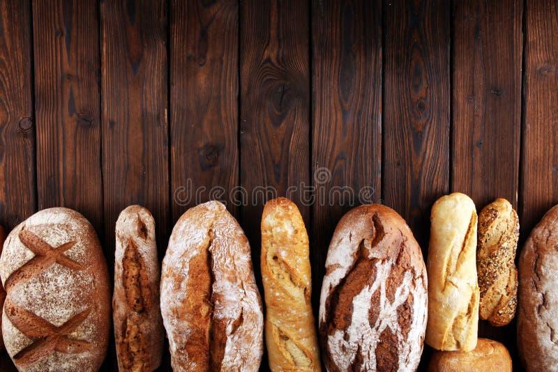 Asortyment piec chlebowe i chlebowe rolki na drewnianym stołowym tle zdjęcia stock