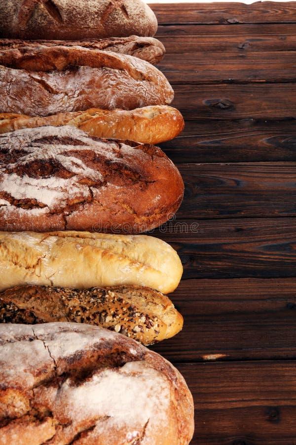 Asortyment piec chlebowe i chlebowe rolki na drewnianym stołowym tle zdjęcie stock