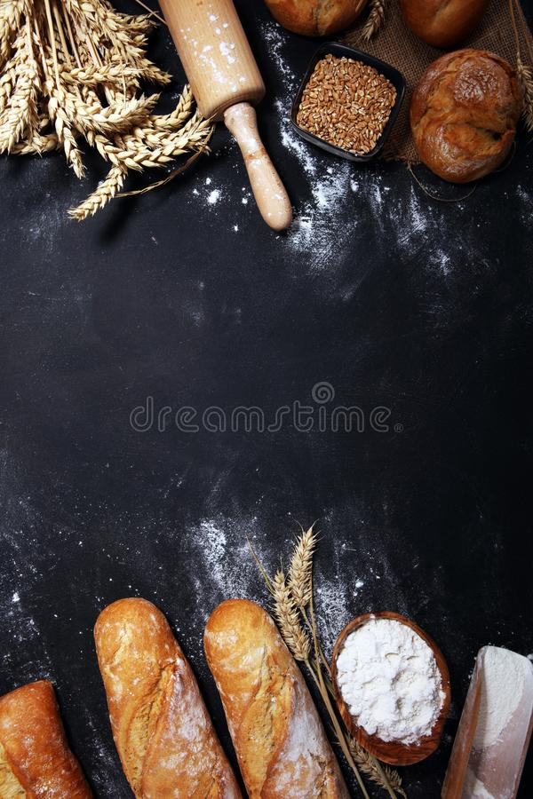 Asortyment piec chlebowe i chlebowe rolki na nieociosanym czarnym piekarnia sto?u tle obraz royalty free