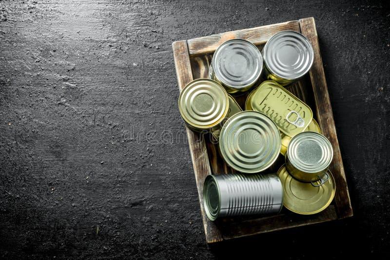 Asortyment różni rodzaje blaszane puszki z konserwować jedzeniem na tacy fotografia stock
