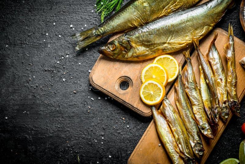 Asortyment różni rodzaje uwędzona ryba na tnących deskach zdjęcia stock