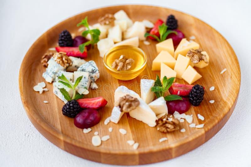 Asortyment różni sery na drewnianym półmisku zdjęcie stock
