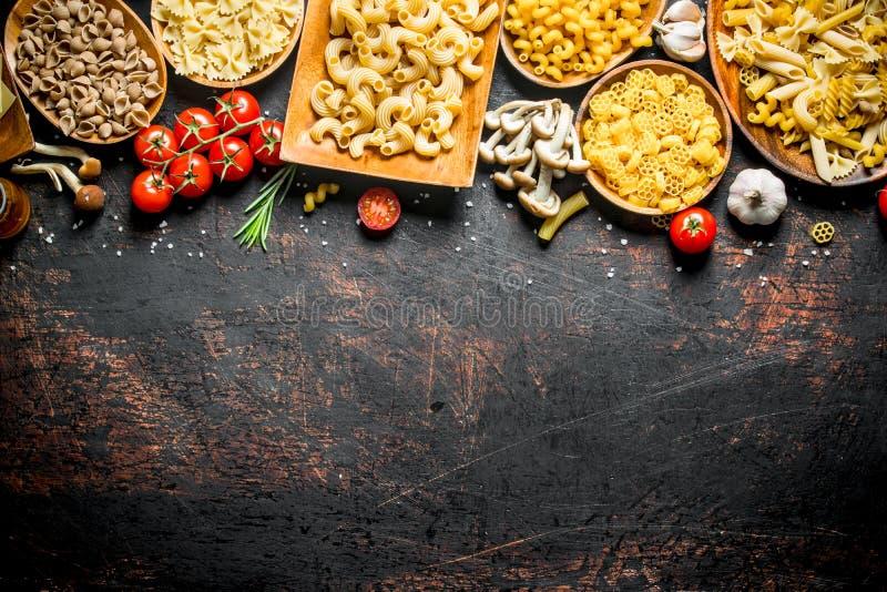Asortyment różni typy surowy makaron z pieczarkami, pomidorami i czosnkiem, fotografia royalty free