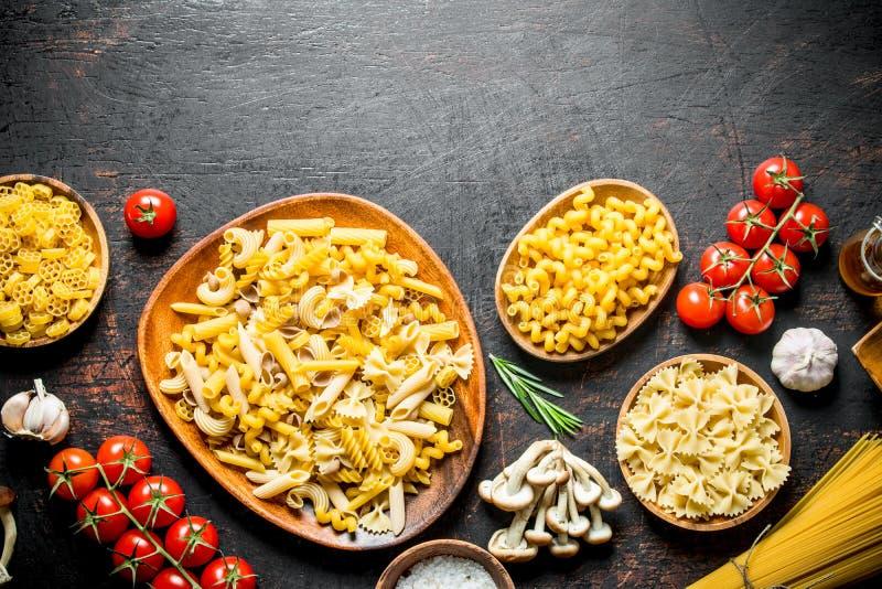 Asortyment różni typy surowy makaron z pieczarkami, pomidorami i czosnkiem, zdjęcia royalty free