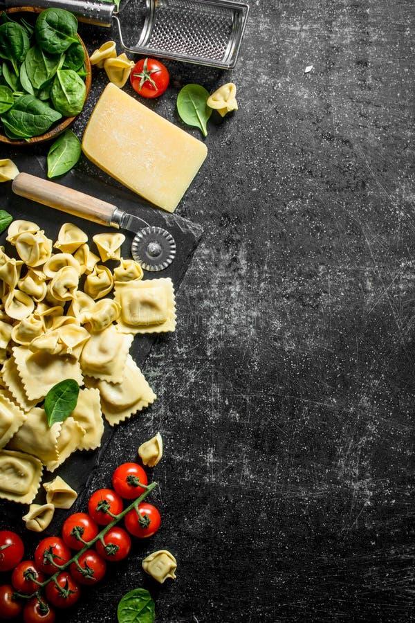 Asortyment różni typy surowy makaron z serem, pomidorami i ziele, obrazy stock