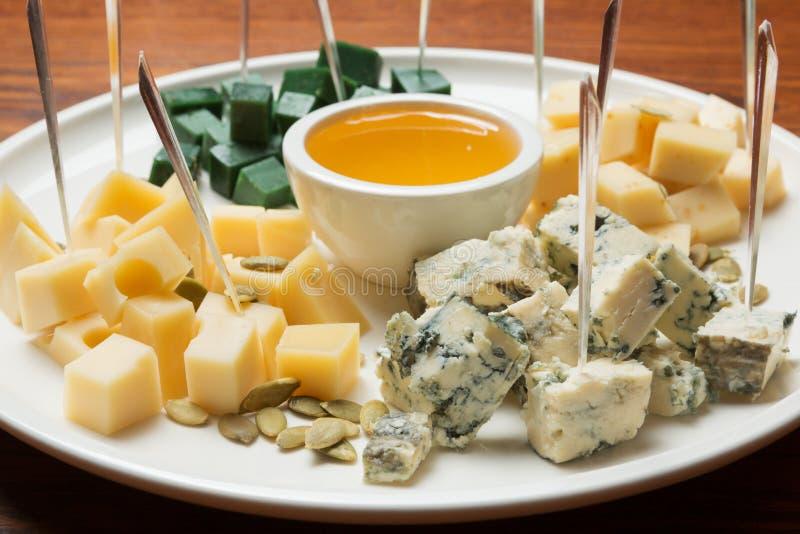Asortyment sery na talerzu, ser diced, miód w pucharze, w górę fotografia stock