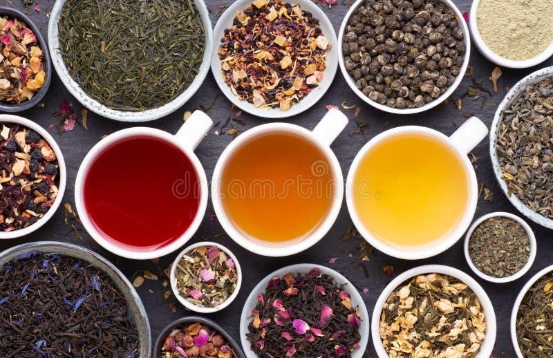 Asortyment suszonych liści herbaty, owoców i ziół w miseczkach i filiżankach herbaty obrazy stock