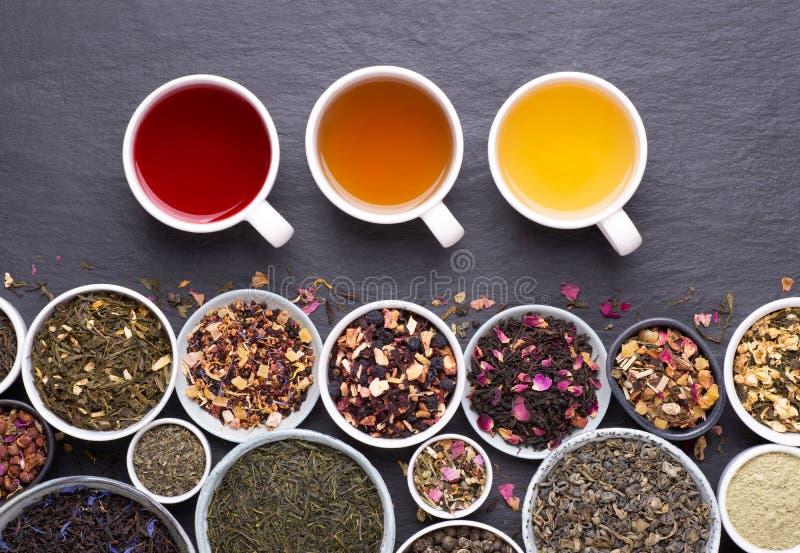 Asortyment suszonych liści herbaty, owoców i ziół w miseczkach i filiżankach herbaty obrazy royalty free