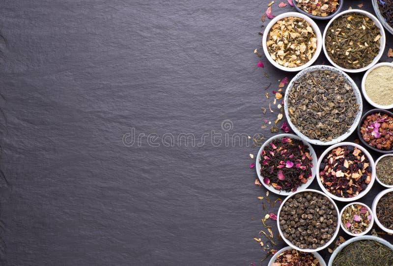 Asortyment suszonych liści herbaty, owoców i ziół w miseczkach zdjęcie stock