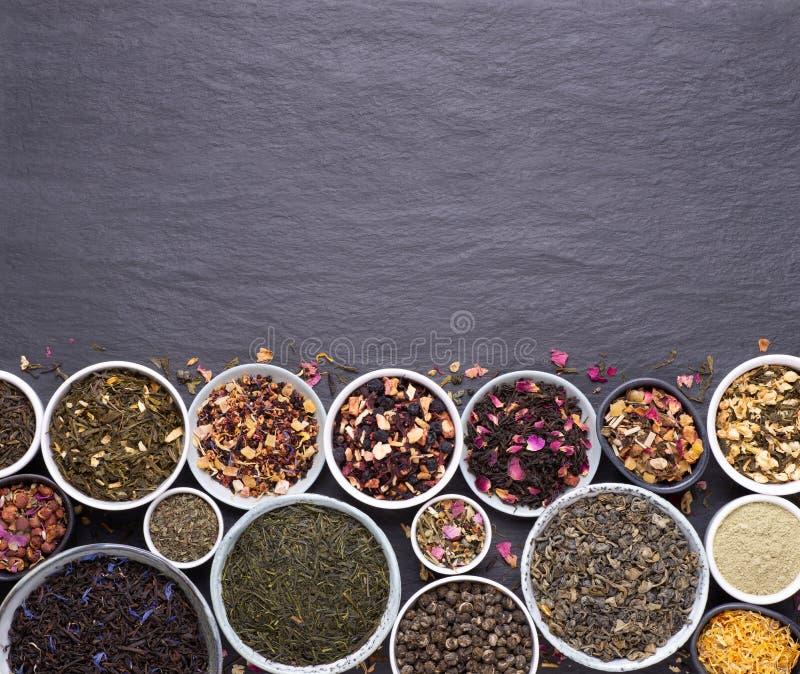 Asortyment suszonych liści herbaty, owoców i ziół w miseczkach na ciemnym, kamiennym tle obraz stock