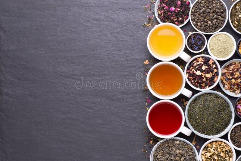 Asortyment suszonych liści herbaty, owoców i ziół w miseczkach na ciemnym, kamiennym tle obrazy royalty free