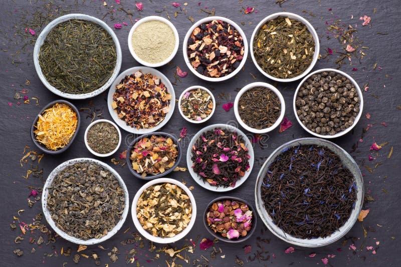 Asortyment suszonych liści herbaty, owoców i ziół w miseczkach na ciemnym, kamiennym tle zdjęcia stock