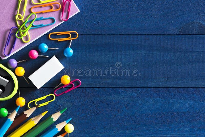 Asortyment szkolny materiały tak jak papierowe klamerki, szpilki, notatnik, pióra, ołówki, władcy, nożyce kłama na stole z przest fotografia royalty free