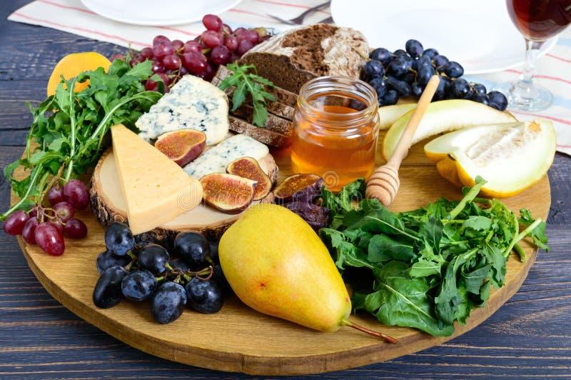 Asortyment zakąska: winogrona, ser, błękitny ser, figi, melon, arugula, zbożowy chleb, miód zdjęcie royalty free