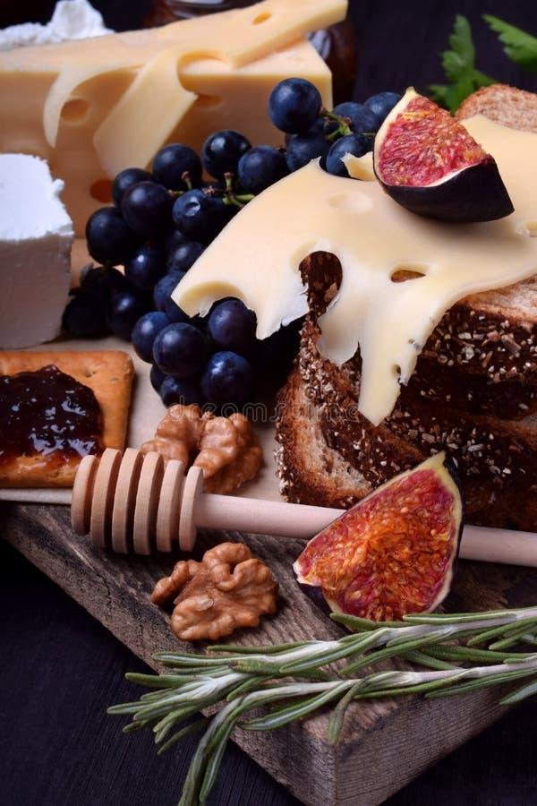 Asortyment zakąski: różni rodzaje ser, krakers, winogrona, dokrętki, oliwny marmoladowy, figi i oliwki, obrazy royalty free
