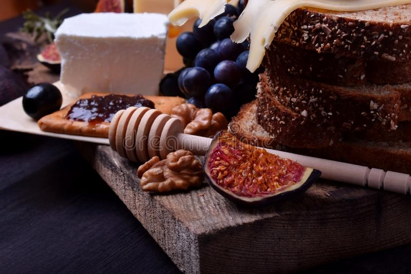 Asortyment zakąski: różni rodzaje ser, krakers, winogrona, dokrętki, oliwny marmoladowy, figi i oliwki, fotografia royalty free