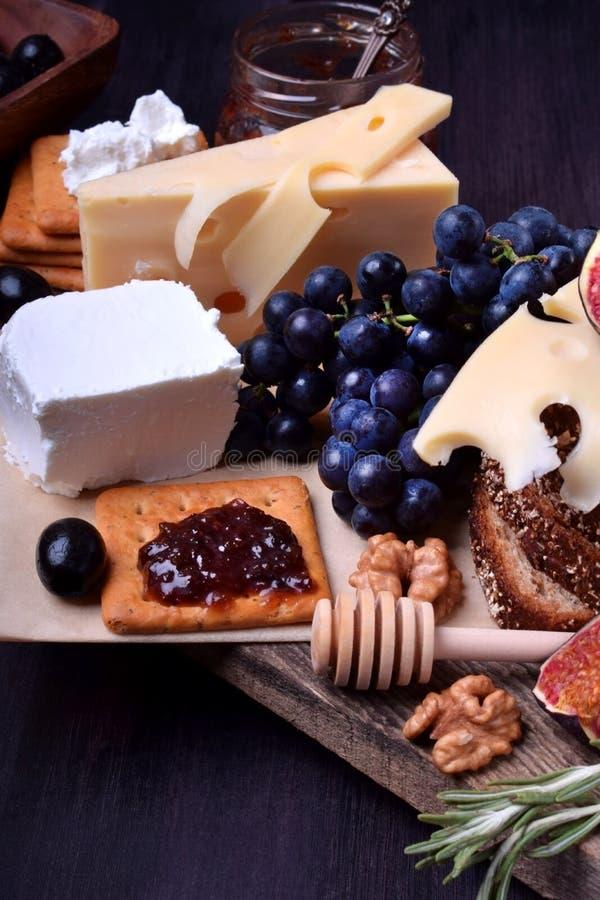 Asortyment zakąski: różni rodzaje ser, krakers, winogrona, dokrętki, oliwny marmoladowy, figi i oliwki, zdjęcie stock