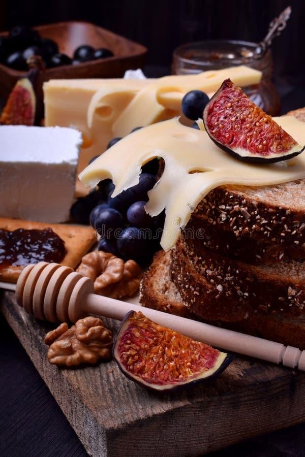 Asortyment zakąski: różni rodzaje ser, krakers, winogrona, dokrętki, oliwny marmoladowy, figi i oliwki, obraz royalty free