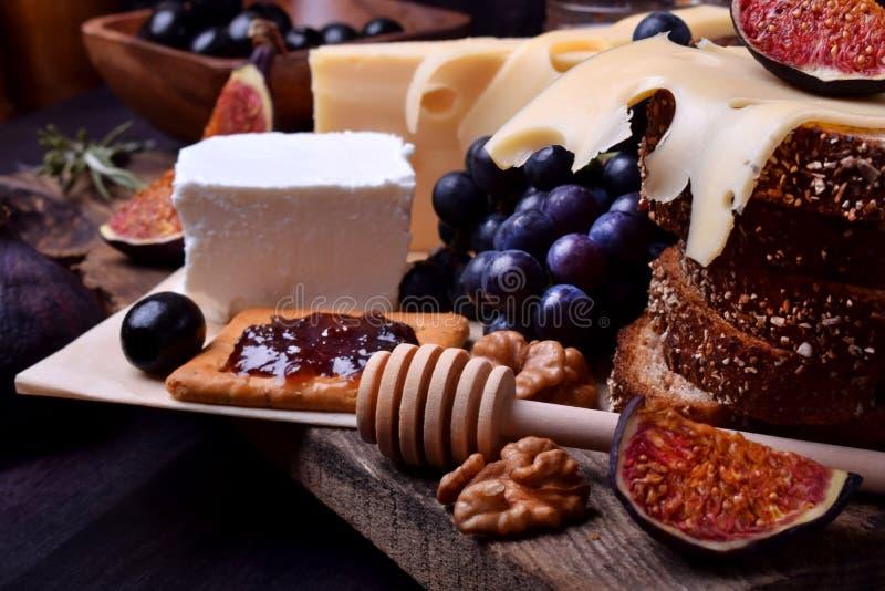 Asortyment zakąski: różni rodzaje ser, krakers, winogrona, dokrętki, oliwny marmoladowy, figi i oliwki, obraz stock