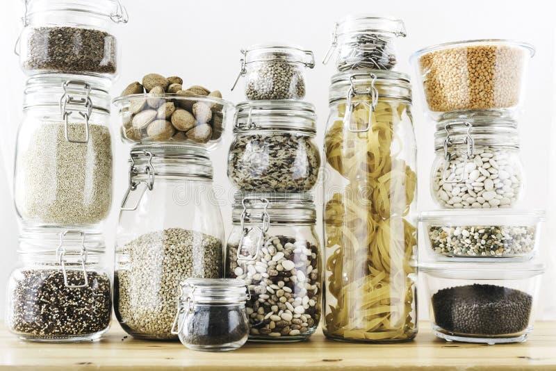 Asortyment zbo?owi produkty i makaron w szklanych sk?adowych zbiornikach na drewnianym stole Zdrowy kucharstwo, czysty ?asowanie, obrazy stock